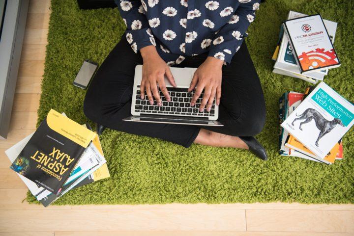 tyttö istuu lattialla kannettava tietokone sylissään kirjojen ympäröimänä