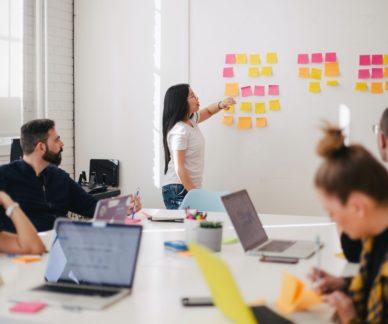 Ihmiset seuraavat neuvotteluhuoneessa naispuolist ayritysvalmentajaa, joka osoittaa taululle jossa on värikkäitä post-it -lappuja.