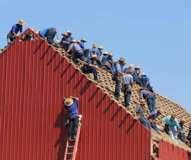 Kymmeniä saman näköisiä miehiä rakentamassa samaa kattoa.