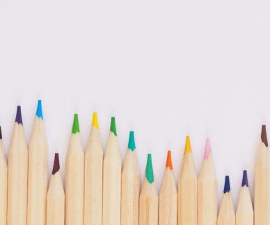 Värikkäitä kyniä valkoisella paperilla